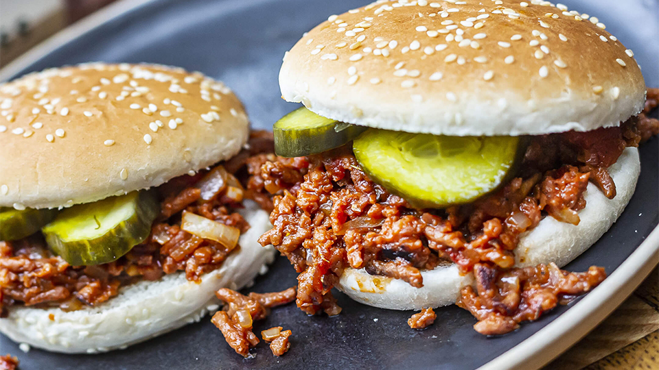 Meat-free mince in a burger bun with slices of gherkin