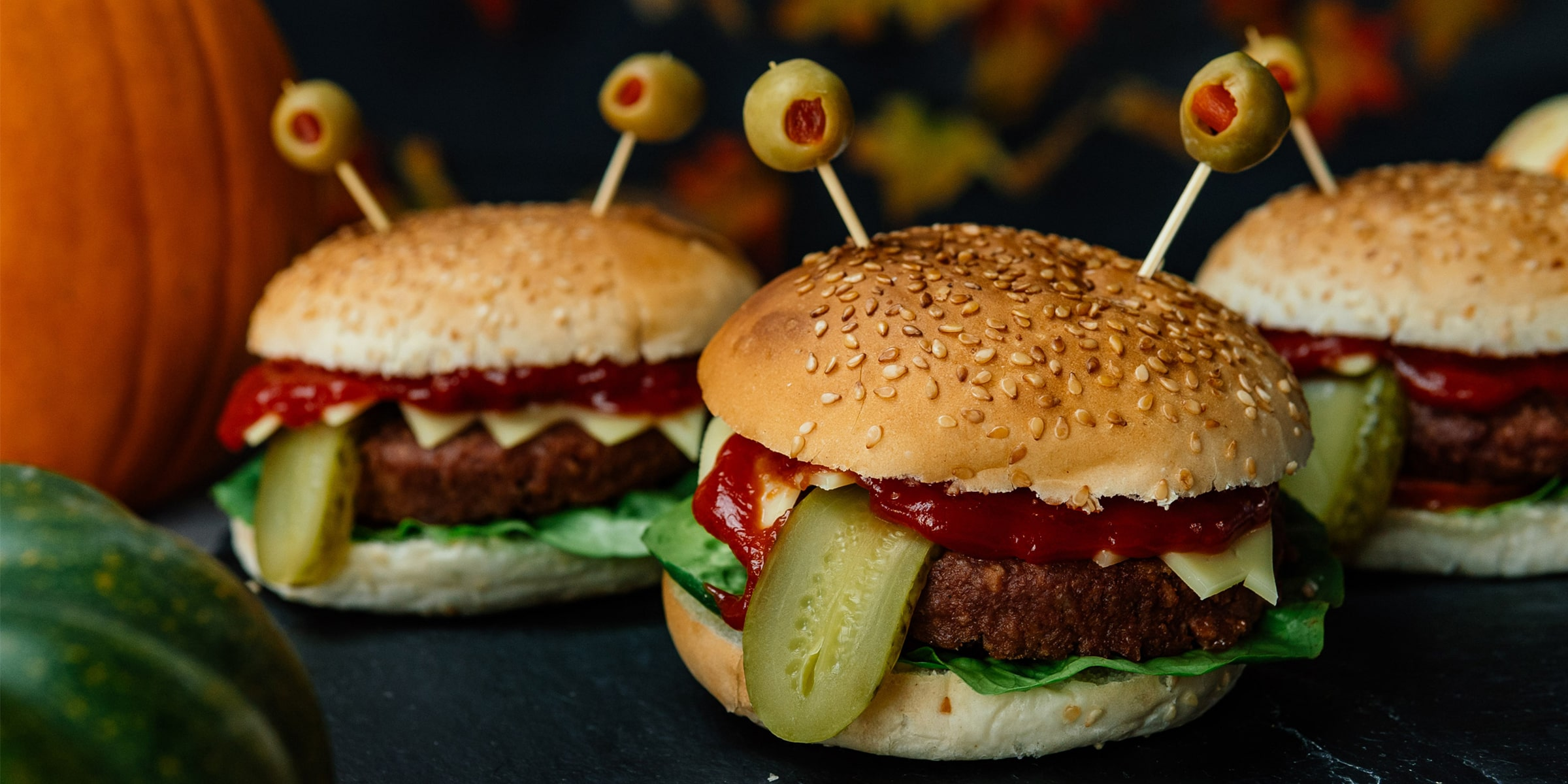 Meat-free burger in a bun with gherkin 'tongue' sticking out and olives on cocktail sticks stuck into the top bread bun for eyes
