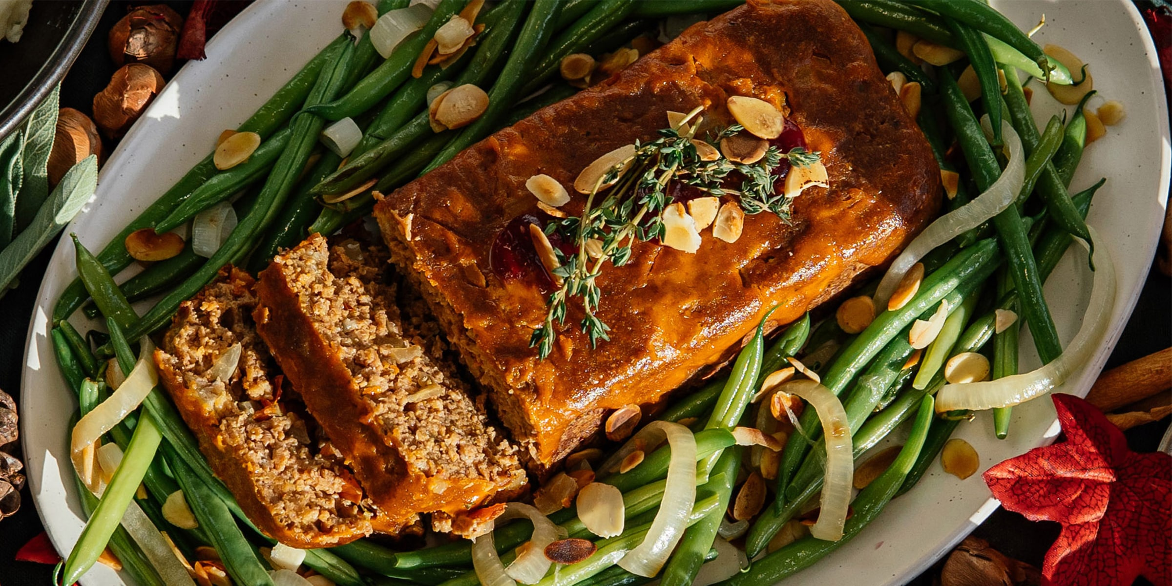 Meat-free meatloaf on a bed of green beans with almonds and onion