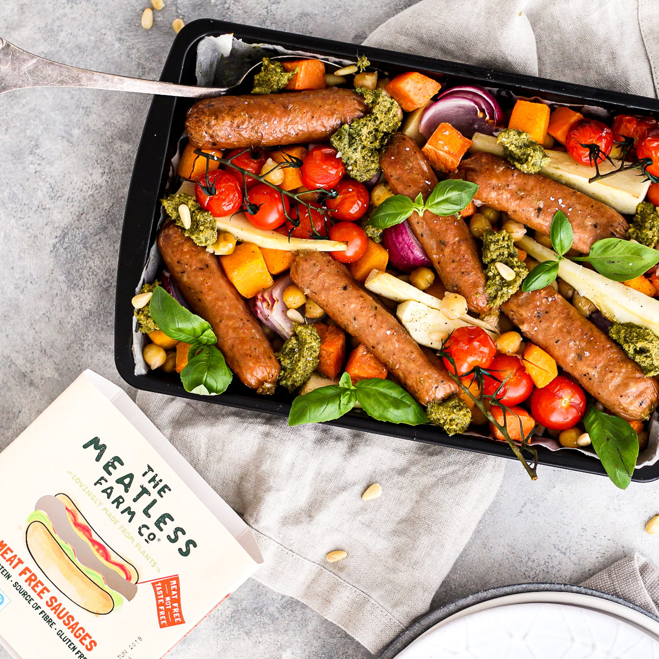 Enjoy this simple summer sharing dish of pesto, sausages and tray baked vegetables