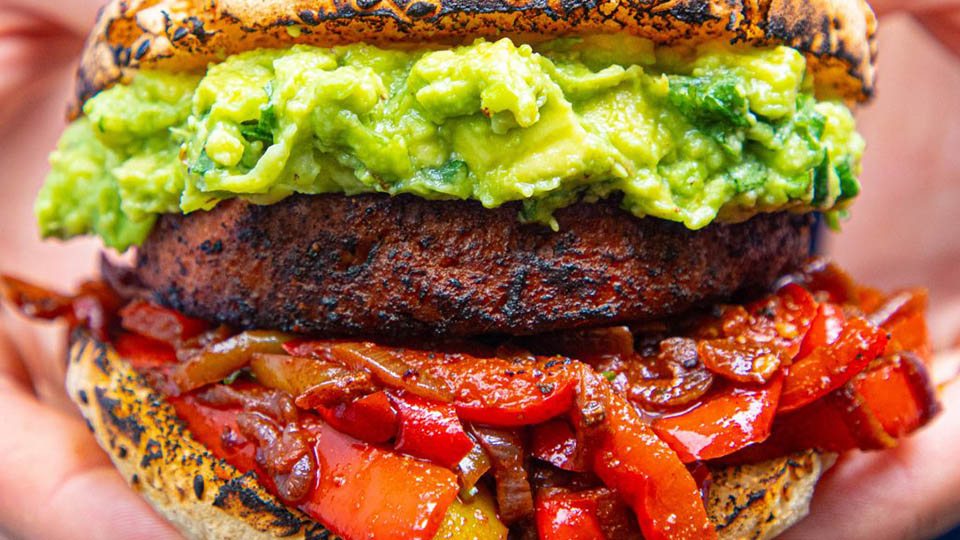 Meat-free burger topped with avocado, grilled peppers and served in a bun